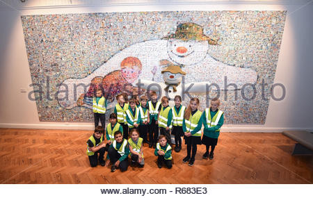 Brighton, UK. 4th Dec, 2018. Children from ; Brackenbury Primary School visit the giant mosaic of the famous Snowman flying with a young boy which was unveiled at Brighton Museum and Art Gallery today to celebrate 40 years of the classic Christmas Snowman book . The mosaic called My Snowman is made up of thousands of festive photographs put together by artist Helen Marshall Credit: Simon Dack/Alamy Live News - Stock Image
