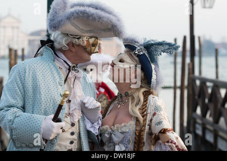 Venice, Italy. 25th Feb, 2014. A masked couple pose with a kiss. The ladies costume showcases her dŽcolletage. Venice Carnivale - Tuesday 25th February. Credit:  MeonStock/Alamy Live News - Stock Image