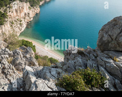 View at empty hidden beach and calm blue sea from the cliff - Stock Image