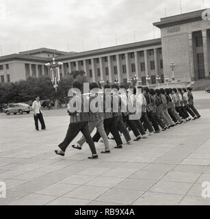 1960, Beijing, China, young chinese women wearing civilian clothiing and carrying weapoings doing military marching exercises in Tiananmen square outside the 'Great Hall of the People', the People's National Congress building, the Chinese Parliament. The are preparing for 'National day', which celebrates the end of the Chinese civil war and the establishment of the People's Repubic under Chairman Mao Zedong. - Stock Image