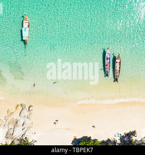 View from above, stunning aerial view of a beautiful tropical beach with white sand and turquoise clear water, long tail boats and people sunbathing,  - Stock Image
