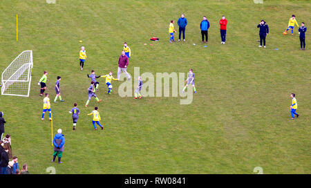 Schoolboys playing an amateur schoolboy sport football  match game - Stock Image