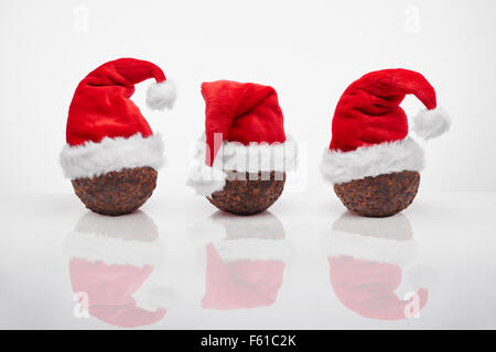 Christmas Puddings with red Santa hats - Stock Image