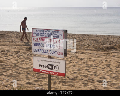 Information sign, sunbed and umbrella for rent om the beach in the holiday destination Ayia Napa Cyprus, free WiFi offered by the municipality - Stock Image