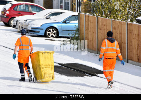 Winter street scene binman binmen or dustmen working & walking  garbage wheely bin on snow covered residential road refuse collection day England UK - Stock Image