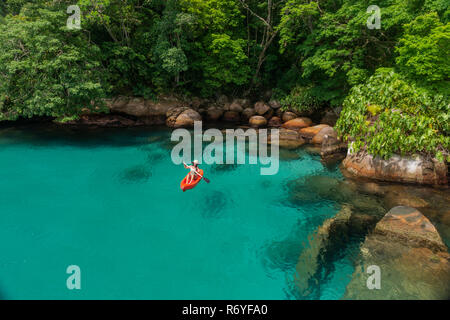 A girl paddles a kayak at the clear waters of Paraty, SE Brazil - Stock Image
