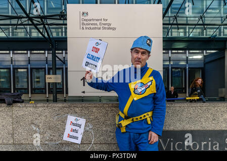 London, UK. October 19th, 2018. 'Commander Neil Godwin Tracy' of International Rescue came from Tracy Island carrying his ship Thunderbird 2 to the Dept for Business, Energy and Industrial Strategy (BEIS) to offer his organisation's assistance, to produce policies which which recognise the desperate need to cut carbon emissions to avoid disastrous global warming and climate change by banning all fracking.  lock himself to the do Credit: Peter Marshall/Alamy Live News - Stock Image