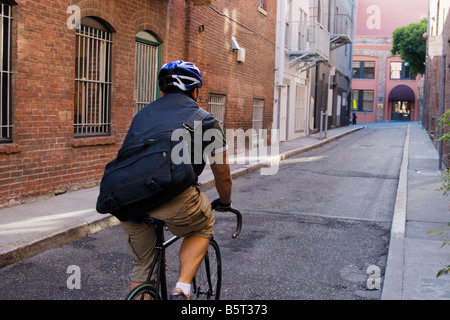 Bike messenger back view rides through an alley San Francisco California USA - Stock Image