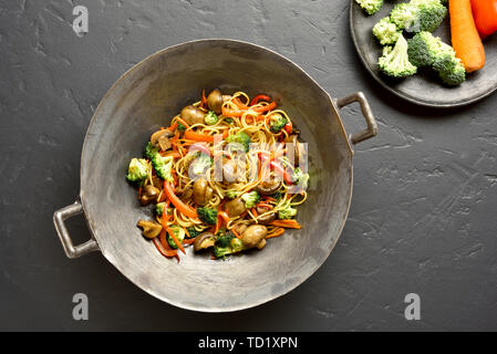 Udon stir-fry noodles with vegetables in wok pan on black stone background. Top view, flat lay - Stock Image