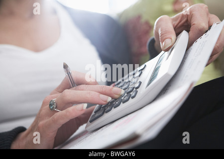 Close-up of woman's hands on calculator - Stock Image