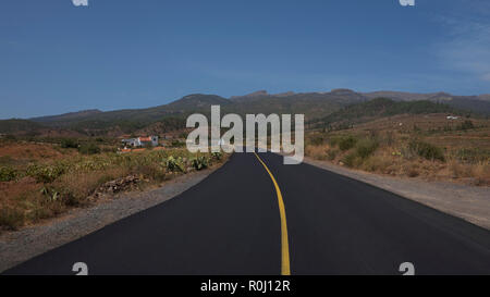 Empty road through Arona Municipality, surrounded by vineyards, terraced farms and wild endemic flora, view towards Teide National Park, Tenerife - Stock Image