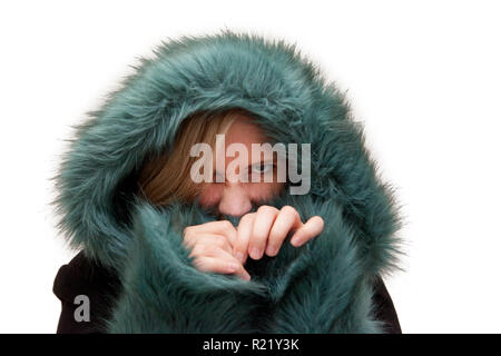 Beautiful blond woman in studio has a green fur hood pulled up and is hiding and making angry face - Stock Image