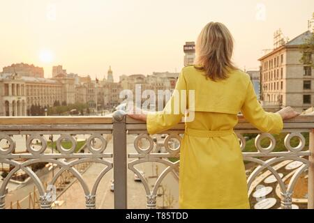 Rear view of woman looking at panorama of evening city. Adult female in yellow raincoat outdoor, copy space, golden hour. - Stock Image