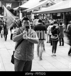 A male tour guide waits, his flag fluttering, for his tour at the Sensō-ji temple (金龍山浅草寺) in Asakusa, Tokyo. - Stock Image
