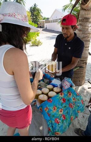 Maldives tourist - a tourist buying a coconut from a local vendor, Ukulhas Island, Alif Alif atoll, the Maldives Asia - Stock Image