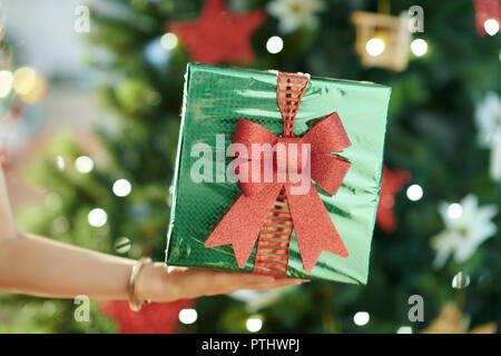 green Christmas present box in a hand of woman near Christmas tree - Stock Image