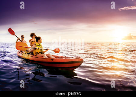 Happy family swims kayaking at sea sunset - Stock Image