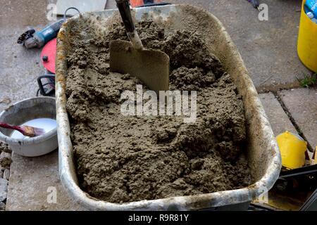 Wheelbarrow full of wet mixed cement with shovel ready to use - Stock Image