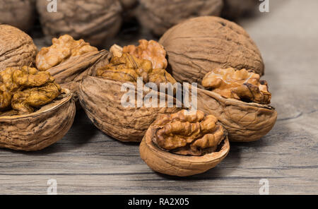 Group of partly peeled nuts with half shells closeup. Cracking of walnuts. Halves of cracked nutshells with nut meat on a wooden background. Walnuts. - Stock Image