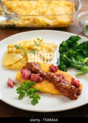 Vegan Schnitzels with a Rhubarb Tomato Sauce served with potato gratin and broccoli. - Stock Image