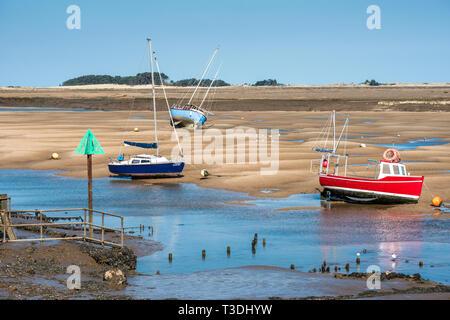 Colourful boats marooned on sandbanks at low tide on East Fleet river estuary at Wells next the sea, North Norfolk coast, East Anglia, England, UK. - Stock Image