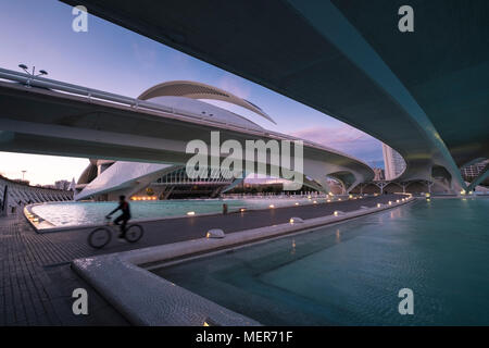A cyclist riding in the Ciudad de las Artes y las Ciencias at twilight, with Palau de les Arts Reina Sofia in the background, Valencia, Spain. - Stock Image