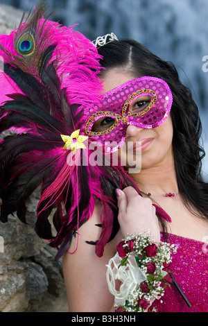 A teenage girl with Mardis Gras mask dressed for prom. - Stock Image
