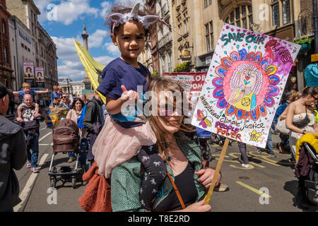 London, UK. 12th May 2019. A woman carries a child on her shouldersand a colourful placard on the XR International Mothers Day March by several thousand mothers, children and some fathers from Hyde Park Corner to a rally filling Parliament Square, backing Extinction Rebellion's call for the drastic and urgent action needed to avert the worst consequences of climate change, including possible human extinction. Our politicians have declared a climate emergency but now need to take real action rather than continuing business as usual which is destroying life on our planet. Peter Marshall/Alamy Li - Stock Image