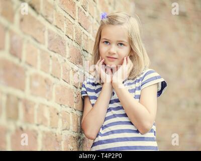 Girl, 10 years, leaning against a wall, Portrait, Germany - Stock Image