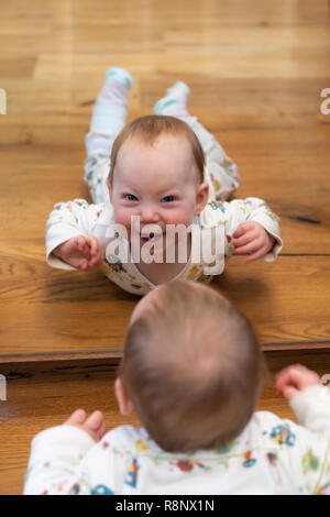 The reflection of a  nine month old baby girl looking in a mirror and smiling at the viewer - Stock Image
