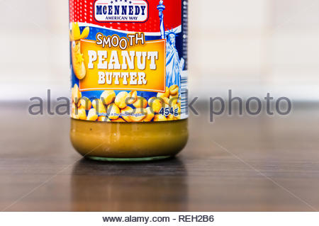 Poznan, Poland - November 20, 2018: Mcennedy Smooth peanut butter in a glass jar standing on a wooden table. - Stock Image