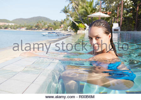 Young woman in swimming pool by beach - Stock Image