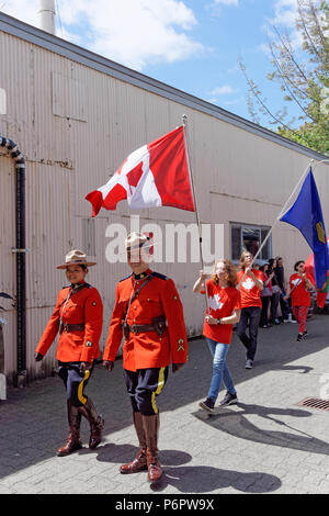 Vancouver, Canada.1st July, 2018. RCMP officers and flag wavers march in the annual Canada Day Parade on Granville Island, Vancouver, British Columbia. This year Canada Day celebrates the country's 151st birthday. Credit: John Mitchell/Alamy Live News - Stock Image