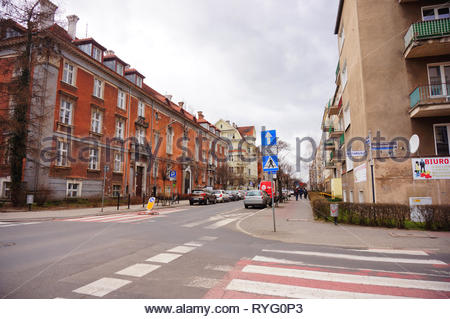 Poznan, Poland - March 8, 2019: Zebra crossing, sidewalk and apartment buildings in the city center. - Stock Image
