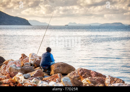 Facing back crouched angler fishing with his rod on the rocks at the sea shore. - Stock Image