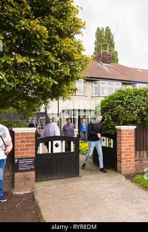 Visitors emerging from the childhood home of John Lennon, Menlove Avenue, Woolton, Liverpool. The museum to the former singer/songwriter and member of - Stock Image