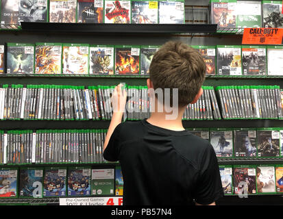 A young boy is buying an xbox one video game at a store for a gamer technology concept. - Stock Image
