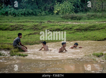 Playing in a puddle, Myanmar - Stock Image