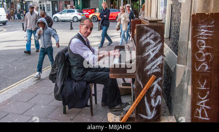 An extremely  talented pianist playing his mobile upright piano in The Lanes of Brighton - Stock Image