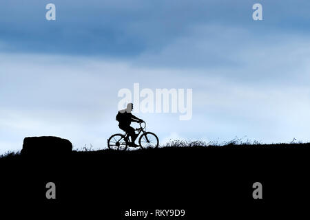 The silhouette of a man riding a bicycle. - Stock Image