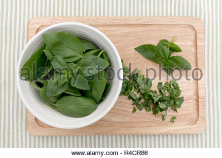 Whole and chopped fresh basil presented on a wooden chopping board - Stock Image