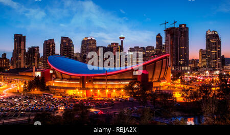 Panorama of Calgary downtown skyline at sunset blue hour showing the iconic Saddledome arena and Calgary Tower in the background with surrounding city - Stock Image