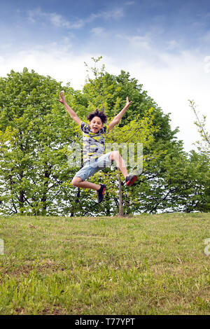 Agile young boy leaping high in the air as he runs across the green grass in a park or garden celebrating his spring freedom - Stock Image