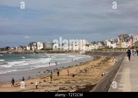 People walking along promenade at seafront. Saint Malo, Brittany, France - Stock Image