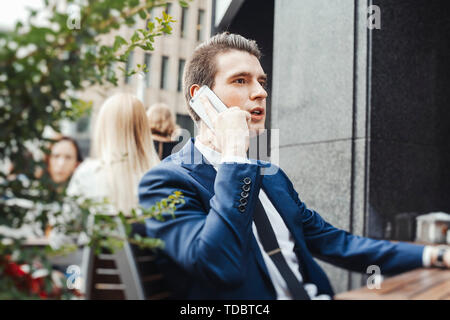 Young pensive attractive businessman talking by mobile phone in street cafe and looking straight. - Stock Image