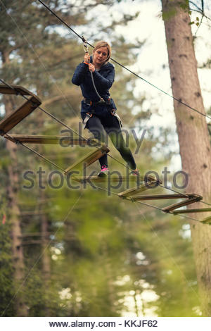 woman on rope high wore bridge - Stock Image