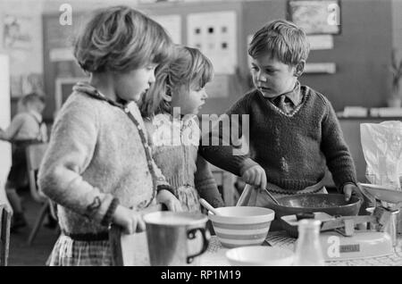 Pancake Making pictures. Five year old pupils from Gawthorpe Infants School, Ussett, West Yorkshire, pictured making pancakes. An experiment thought up by headmistress Margaret Craighan. Picture shows David Laffey (right) with his friends making their pancakes  Picture taken 4th March 1965 - Stock Image