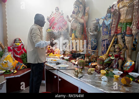 A devout Hindu worshiper prays & meditates in front of statues of deities at a temple in Jamaica, Queens, New York City. - Stock Image
