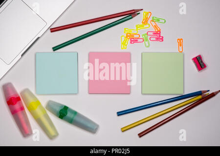 Collection of colored adhesive notes and stationery on work area. Text space, copy space. - Stock Image