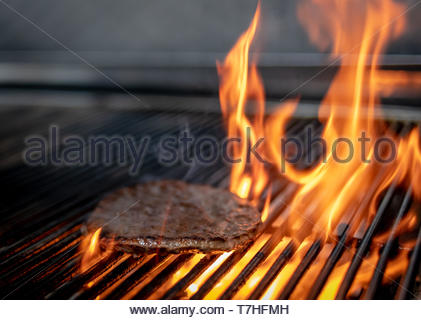 Beef burger being flame grilled in a kitchen - Stock Image